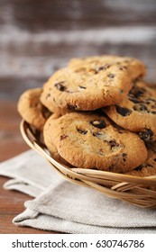 Chocolate chip cookies in basket on brown wooden table