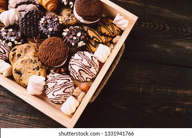 chocolate chip cookies, biscuits, sweets assortment in craft wooden box. sweet food, culinary background. confectionery design concept