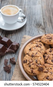 Chocolate chip cookies with coffee on wooden background