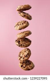 Chocolate chip cookies falling, pink background, food levitation