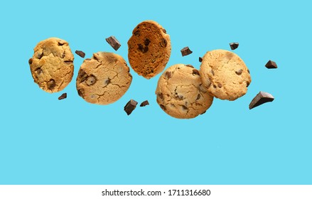 Chocolate chip cookies flying or falling over turquoise blue background. - Shutterstock ID 1711316680