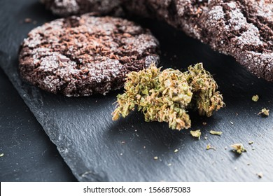 chocolate chip cookies with marijuana, sprinkled with chocolate chips and cannabis, are on a slate dish. Horizontal orientation.