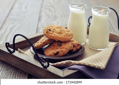 Chocolate chip cookies  with  milk in bottles on wooden tray