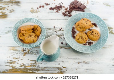 Chocolate chip cookies with milk in jug  on wooden table. Selective focus
