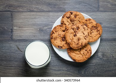 Chocolate chip cookies, milk, rustic wood background, top view