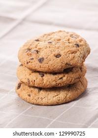 Chocolate chip cookies on brown napkin.