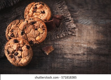 Chocolate chip cookies on dark old wooden table with place for text.,  freshly baked. Selective Focus with Copy space.