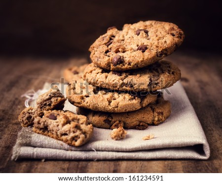 Chocolate chip cookies on linen napkin on wooden table. Stacked chocolate chip cookies close up.