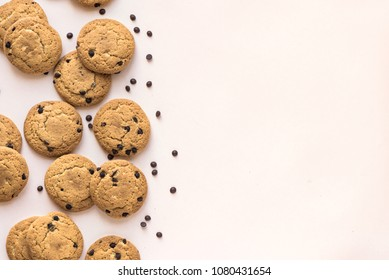 Chocolate chip cookies on pink pastel background, top view, copy space