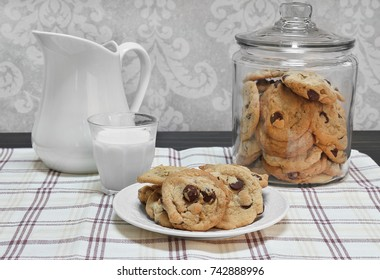 Chocolate chip cookies on a plate and a glass of milk  in front of a glass cookie jar.