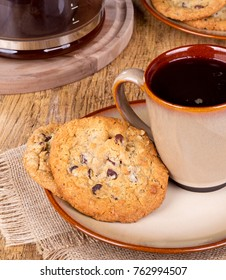 Chocolate chip cookies on a plate with cup of coffee on a wooden table