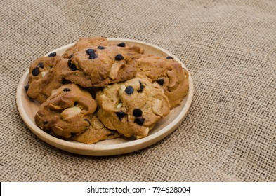 Chocolate chip cookies on wood plate in brown background