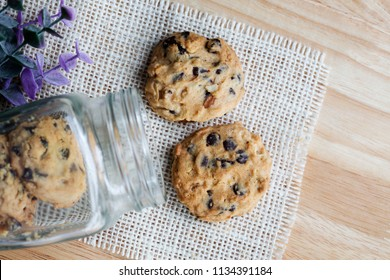Chocolate chip Cookies on wooden desk with glass jar,top view.