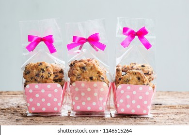 Chocolate chip cookies in plastic bag packaging with ribbon bow.