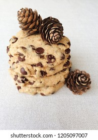 Chocolate chip cookies stack decorated with pine cones, close up, white background. Winter holiday treats
