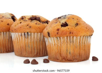 Chocolate chip and cranberry muffin cup cakes with loose chips over white background. Selective focus.