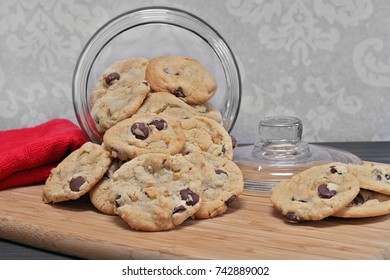 Chocolate chip and walnut cookies spilling out of a glass cookie jar.