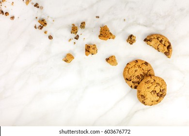 Chocolate chips cookies and crumbs, shot from above on a white marble background, with a place for text