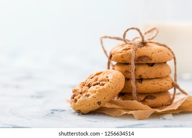 Chocolate chips cookies tied in stack on craft baking paper and glass of milk on pastel blue background with copy space - horizontal tender banner with fresh tasty baked sweet dessert.