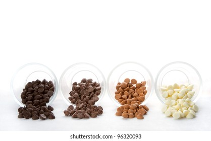 Chocolate chips in four varieties spilling out of glass containers, white background