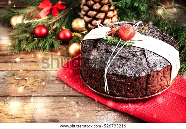 Chocolate Christmas Pudding served on plate with xmas decorations. Wooden background. Toned.