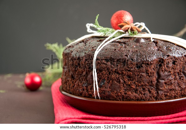 Chocolate Christmas Pudding served on plate with xmas decorations.