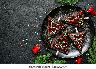 Chocolate christmas tree on a black plate over dark slate, stone or concrete background.Top view with copy space.