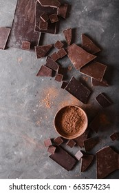 Chocolate  chunks and cocoa powder on gray abstract background