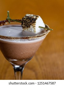 chocolate cocktail with marshmallow vodka garnished with a gram cracker rim and a toasted marshmallow