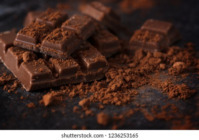 chocolate and cocoa powder on a dark slate plate, macro shot, selected focus, narrow depth of field