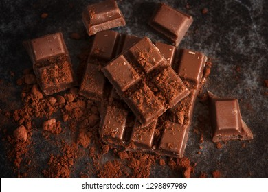 chocolate and cocoa powder on a dark slate plate, high angle view from above, selected focus