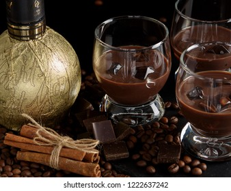 Chocolate, coffee, creamy liqueur, cocktail with coffee beans, chocolate and cinnamon. On a black background. Christmas alcoholic drink.