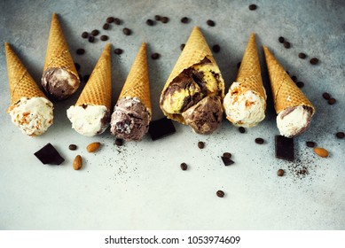 Chocolate and coffee ice cream in waffle cone with coffee beans on grey stone background. Summer food concept, copy space. Healthy gluten free ice-cream. Top view