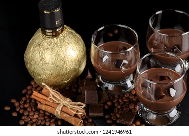 Chocolate, coffee liqueur in glass glasses with ice cubes. With coffee beans, chocolate, cinnamon and a bottle of liqueur in gold foil. On a black background