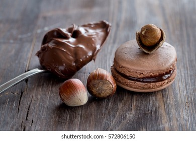 Chocolate and coffee macaroons or macarons on old dark brown wooden background