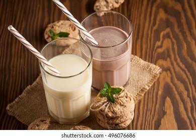 Chocolate, coffee, milk, banana shake on wooden background. Smoothie with cookies. Milkshake. Protein diet. Healthy food concept.
