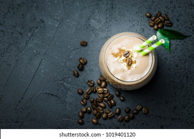 Chocolate coffee smoothie and coffee beans on dark concrete background. Selective focus, space for text. Top view, space for text, close up.