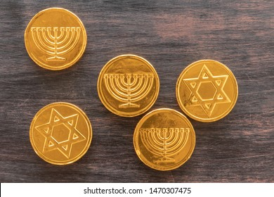 Chocolate coins with Jewish symbols on a wooden background.Menorah and Magen David. Top view.