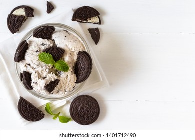 Chocolate cookie and ice cream in a glass bowl with mint leaf on white wooden background, summer sweet and dessert