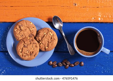 Chocolate cookies with blue cup of hot coffee on colorful wooden table, top view