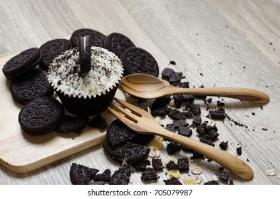 Chocolate cookies and Chocolate cup cake with cream filling put on table with spoon and fork