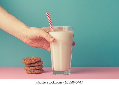 Chocolate cookies and a glass of milk in hand on a pink background.