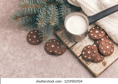 Chocolate cookies with jar of hot milk on the old wooden cutting board. Gray slate background. Top view. Cozy evening