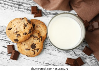Chocolate cookies and napkin on wooden background, top view