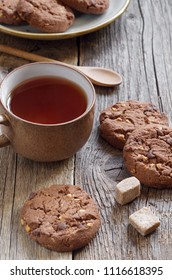 Chocolate cookies with nuts and cup of tea on the old wooden table