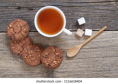 Chocolate cookies with nuts and cup of tea on the old wooden table, top view
