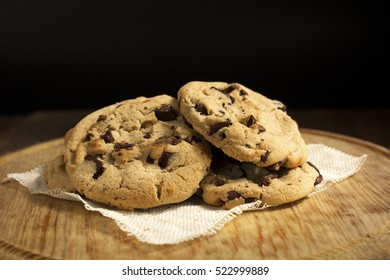 Chocolate cookies on a napkin, on wooden table. Chocolate chip cookies shot, closeup