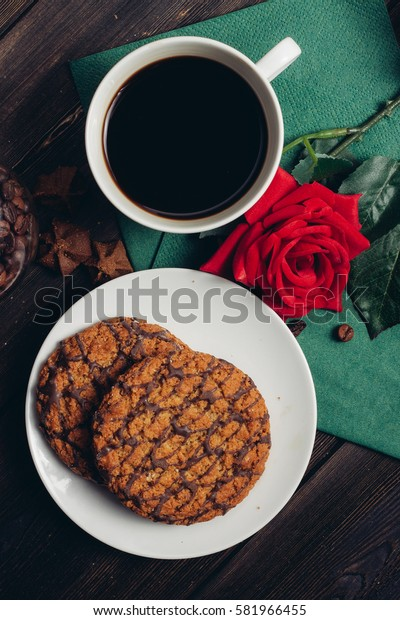 Chocolate cookies on a plate, red rose on a green napkin, coffee beans, coffee mug.