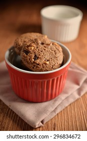 Chocolate cookies on red bowl and pink napkin on wooden background. Chocolate chip cookies shot on colored cloth, closeup.
