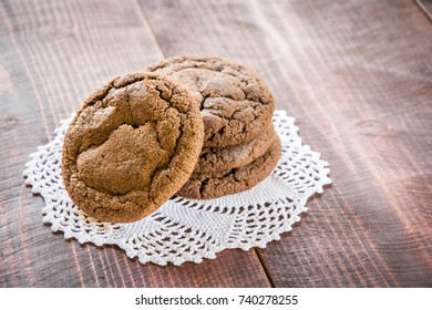Chocolate cookies on white handmade doily on dark brown wooden table